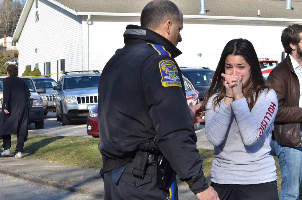 . An unidentified woman asks a police officer for information about a teacher after a shooting spree threw Sandy Hook Elementary School in Newtown into turmoil Friday morning. Melanie Stengel/Register