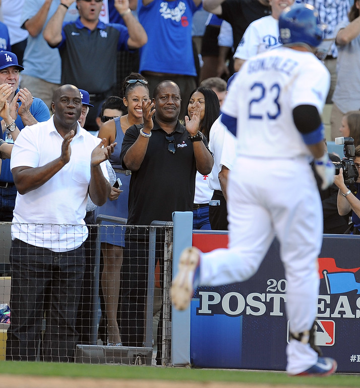 . Magic Johnson claps as the Dodgers\' Adrian Gonzalez heads for the dugout after his homer in the 8th during game 5 of the NLCS against the Cardinals at Dodger Stadium Wednesday, October 16, 2013. The Dodgers beat the Cardinals 6-4. (Photo by Hans Gutknecht/Los Angeles Daily News)