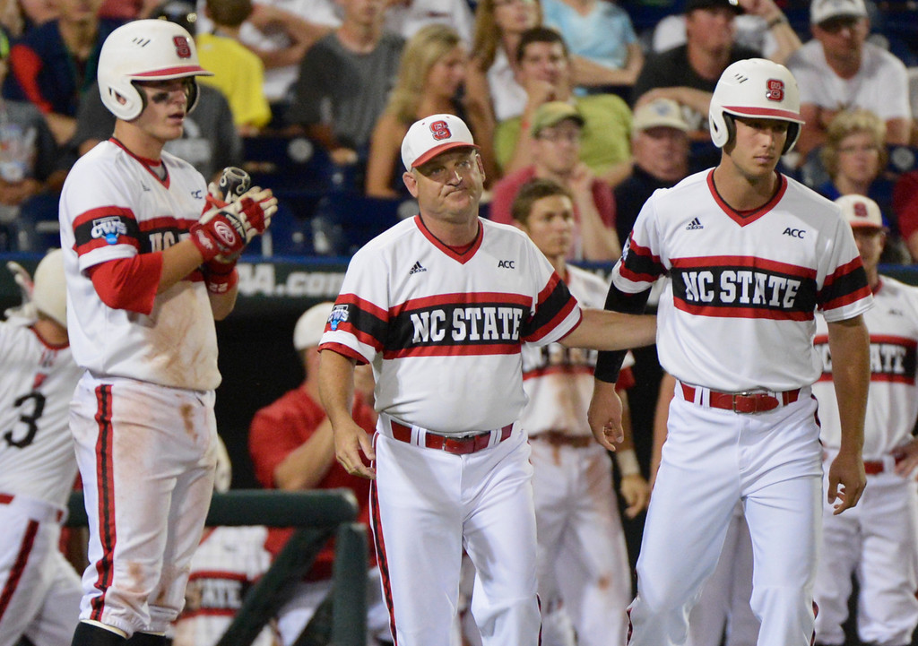 . North Carolina State coach Elliott Avent, center, follows his team against UCLA in the ninth inning of an NCAA College World Series baseball game in Omaha, Neb., Tuesday, June 18, 2013. UCLA won 2-1. (AP Photo/Ted Kirk)