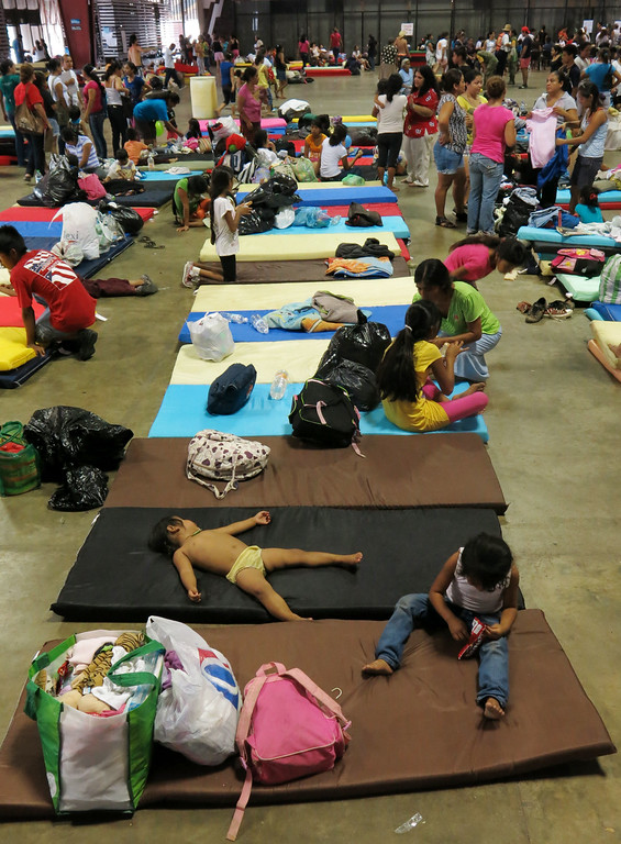 . Residents from the village La Pintada rest inside the Acapulco Convention Center after their town was affected by flooding, in Acapulco, Mexico, Thursday, Sept. 19, 2013.  (AP Photo/Michael Weissenstein)