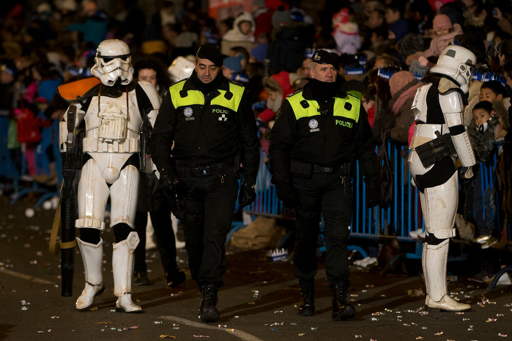 . Two police officers pass by two performers dressed as Star Wars Stormtroopers during the \'Cabalgata de Reyes\' or Epiphany parade in Madrid, Tuesday, Jan. 5, 2016. The traditional parade marks the eve of the Epiphany, a Christian holiday celebrating the story of the three wise men believed to have followed a bright star to offer gifts of gold, frankincense and myrrh to the newborn Jesus in Bethlehem. (AP Photo/Paul White)