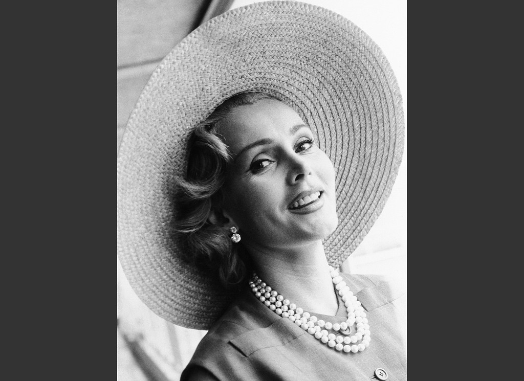 . FILE - In a July 14, 1955 file photo, Zsa Zsa Gabor arrives at London Airport from Paris, in a Crimson dress and a straw hat. Gabor died Sunday, Dec. 18, 2016, of a heart attack at her Bel-Air home, her husband, Prince Frederic von Anhalt, said. She was 99. (AP Photo)