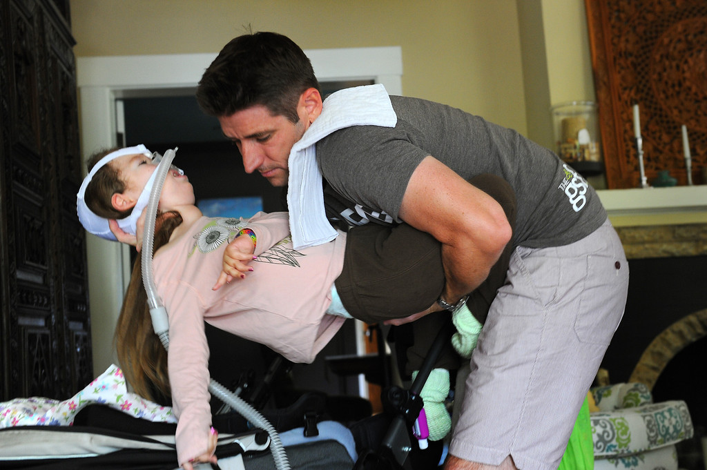 . Bill Strong lifts his daughter Gwendolyn in their Santa Barbara home. Gwendolyn was born with spinal muscular atrophy. (Photo by Michael Owen Baker/Los Angeles Daily News)