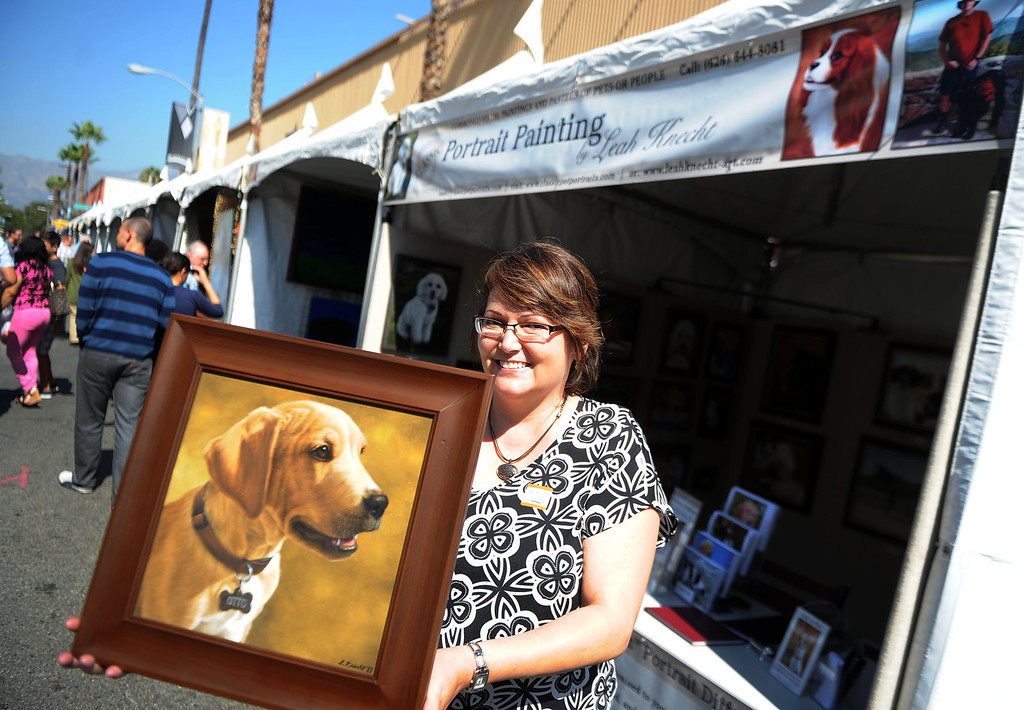 . Artist Leah Knecht with one of her favorite paintings during the 8th Annual Pasadena ARTWalk along El Molino Avenue between Colorado Boulevard and Green Street in Pasadena, Calif., on Saturday, Oct. 12, 2013. The ArtWalk features over 30 participating artists, art sales, gallery walks, musical performances and other activities.   (Keith Birmingham Pasadena Star-News)