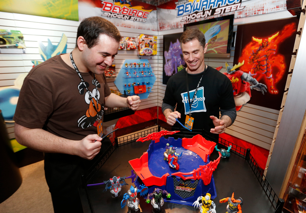 Description of . Demonstrators Nick Latrenta, left, and Brian McMullan battle head-to-head in the BEYBLADE SHOGUN STEEL OCTAGON SHOWDOWN set in Hasbroís showroom at the American International Toy Fair, Friday, Feb. 8, 2013, in New York.  BEYBLADE SHOGUN STEEL BEYWARRIOR battlers compete to be the last battler spinning in this new arena, which allows for spinning, crashing, and ricocheting off the walls. (Photo by Jason DeCrow/Invision for Hasbro/AP Images)