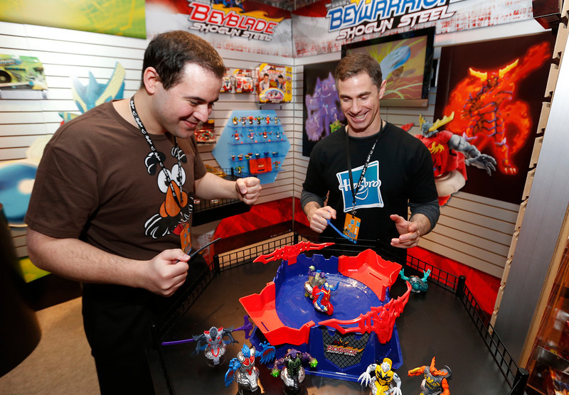 . Demonstrators Nick Latrenta, left, and Brian McMullan battle head-to-head in the BEYBLADE SHOGUN STEEL OCTAGON SHOWDOWN set in Hasbroís showroom at the American International Toy Fair, Friday, Feb. 8, 2013, in New York.  BEYBLADE SHOGUN STEEL BEYWARRIOR battlers compete to be the last battler spinning in this new arena, which allows for spinning, crashing, and ricocheting off the walls. (Photo by Jason DeCrow/Invision for Hasbro/AP Images)