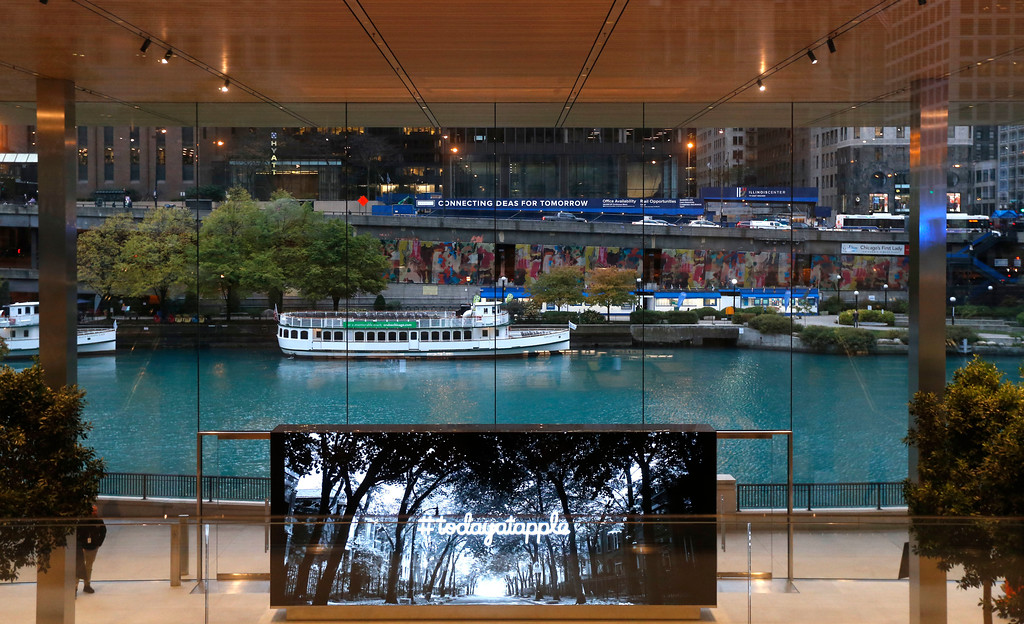 . A large monitor gives consumers an overview of the events of the day at the new Apple Michigan Avenue store along the Chicago River Friday, Nov. 3, 2017, in Chicago. Apple released the Apple iPhone X Friday. (AP Photo/Charles Rex Arbogast)