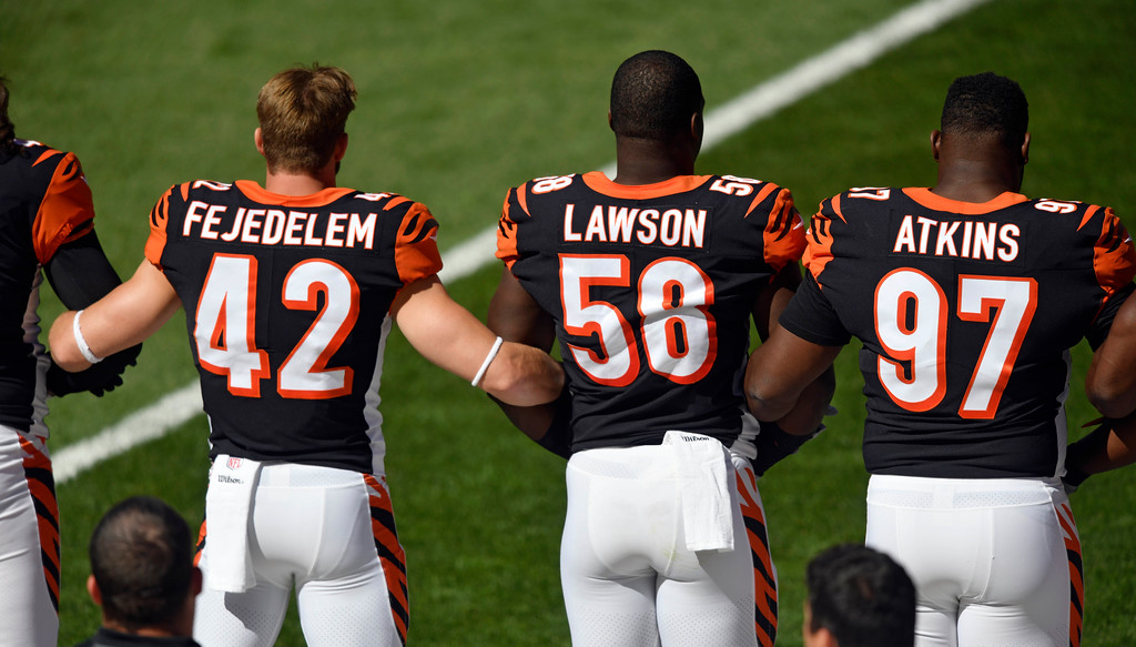 . Members of the Cincinnati Bengals lock arms during the national anthem before an NFL football game against the Cleveland Browns, Sunday, Oct. 1, 2017, in Cleveland. (AP Photo/David Richard)