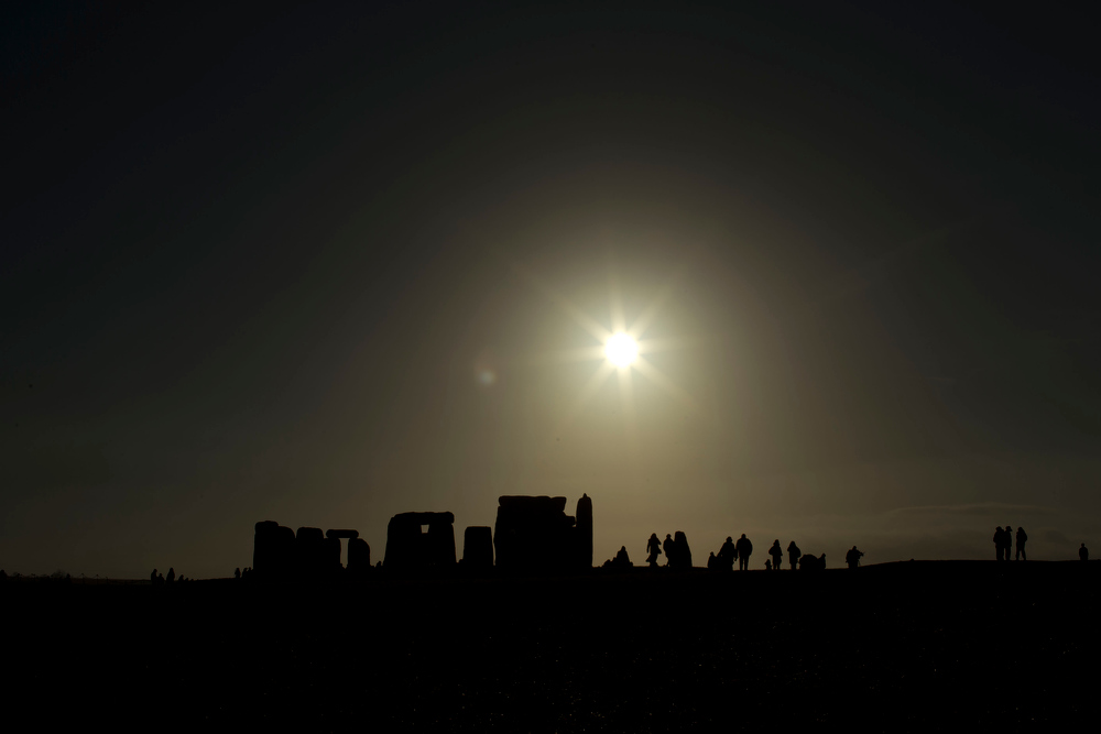 Description of . People are silhouetted as the sun rises above the ancient stone circle of Stonehenge, in southern England, as access to the site is given to druids, New Age followers and members of the public on the annual Winter Solstice, Friday, Dec. 21, 2012.  Doomsday hour is here and so still are we.  According to legend, the ancient Mayans' long-count calendar ends at midnight Thursday, ushering in the end of the world. Didn't happen.