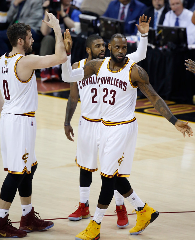 . Cleveland Cavaliers forward LeBron James (23) celebrates with Kevin Love (0) and Kyrie Irving (2) during the first half against the Golden State Warriors in Game 4 of basketball\'s NBA Finals in Cleveland, Friday, June 9, 2017. (AP Photo/Ron Schwane)