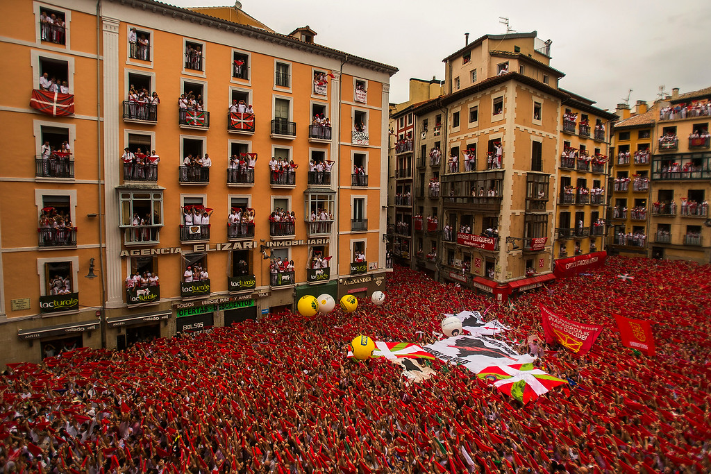 """. Revelers hold up traditional red neckties during the launch of the \""""Chupinazo\"""" rocket, to celebrate the official opening of the 2014 San Fermin fiestas in Pamplona, Spain, Sunday, July 6, 2014. Revelers from around the world turned out here to kick off the festival with a messy party in the Pamplona town square, one day before the first of eight days of the running of the bulls glorified by Ernest Hemingway\'s 1926 novel \""""The Sun Also Rises.\"""" (AP Photo/Andres Kudacki)"""