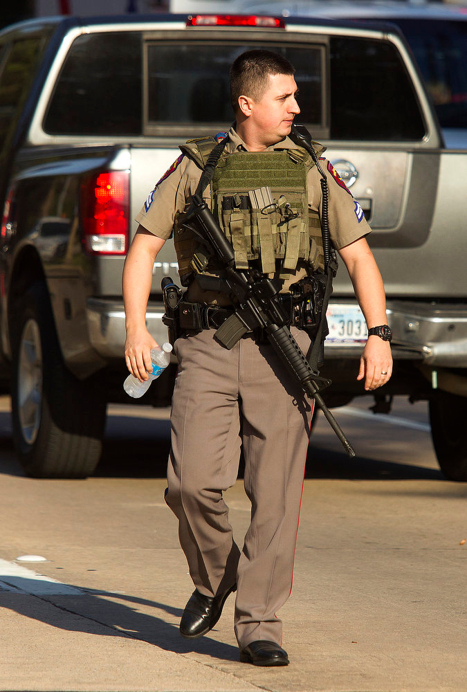 . A heavily armed policeman walks along at the Lone Star College North Harris campus  Tuesday Jan.  22, 2013 in Houston.   A shooting at the Texas community college wounded three people Tuesday and sent some students fleeing for safety while others with medical training helped tend the wounded.  (AP Photo/ Patric Schneider)