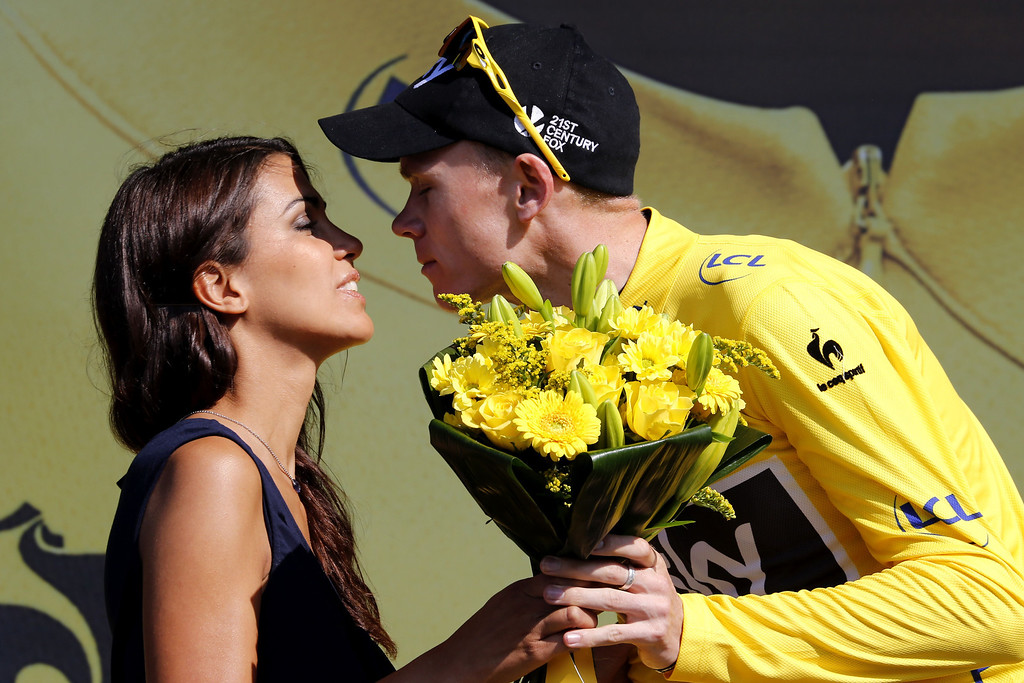 . Britain\'s Christopher Froome kisses a hostess as he celebrates his overall leader\'s yellow jersey on the podium at the end of the 197 km tenth stage of the 100th edition of the Tour de France cycling race on July 9, 2013 between Saint-Gildas-des-Bois and Saint-Malo, northwestern France.   PASCAL GUYOT/AFP/Getty Images