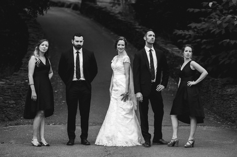 The bride standing between her friends in black suits and dresses, making silly, ironic poses as if they are pretending to be in a magazine shoot.
