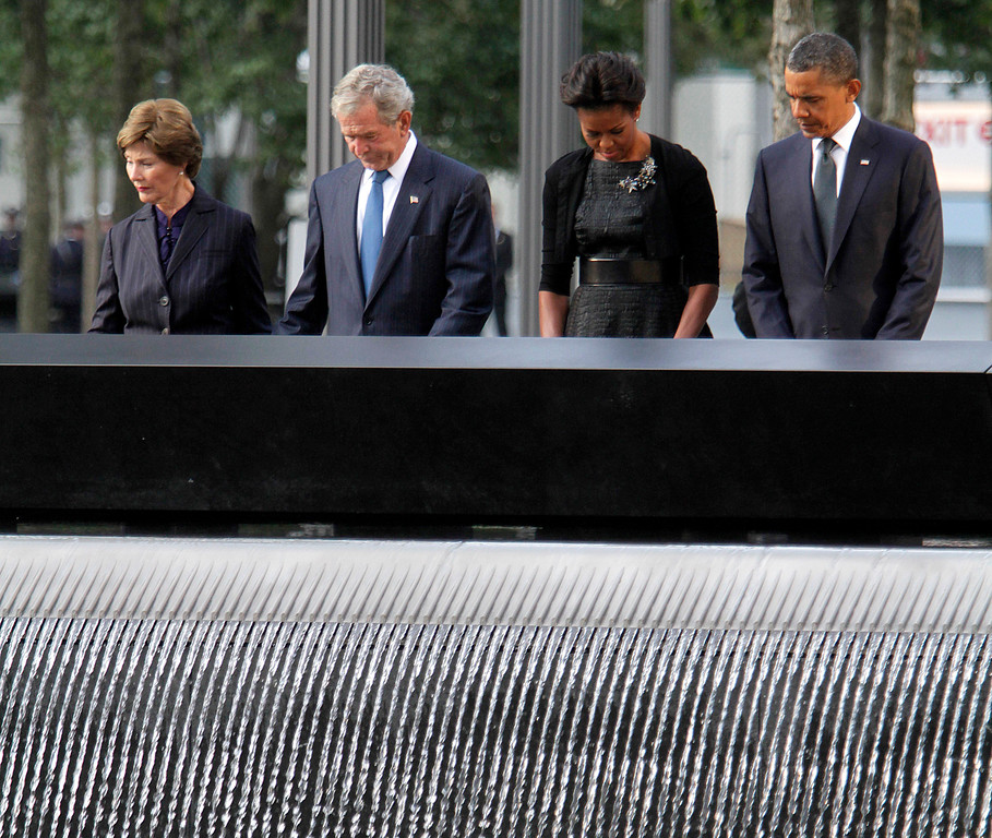 . President Barack Obama, right, first lady Michelle Obama, second from right, former President George W. Bush, second from left, and former first lady Laura Bush observe a moment of silence at the National September 11 Memorial for a ceremony marking the 10th anniversary of the attacks at World Trade Center, Sunday, Sept. 11, 2011, in New York.  (AP Photo/Mary Altaffer)