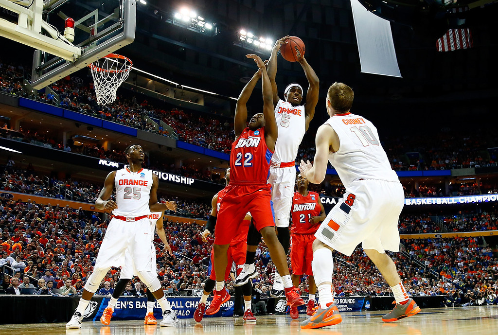 . BUFFALO, NY - MARCH 22: C.J. Fair #5 of the Syracuse Orange and Kendall Pollard #22 of the Dayton Flyers fight for a rebound during the third round of the 2014 NCAA Men\'s Basketball Tournament at the First Niagara Center on March 22, 2014 in Buffalo, New York.  (Photo by Jared Wickerham/Getty Images)