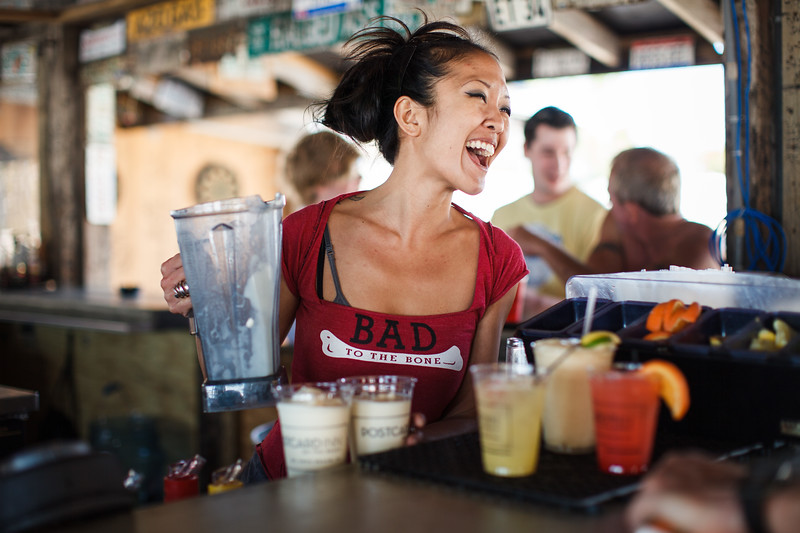 A bartender laughing and making drinks.