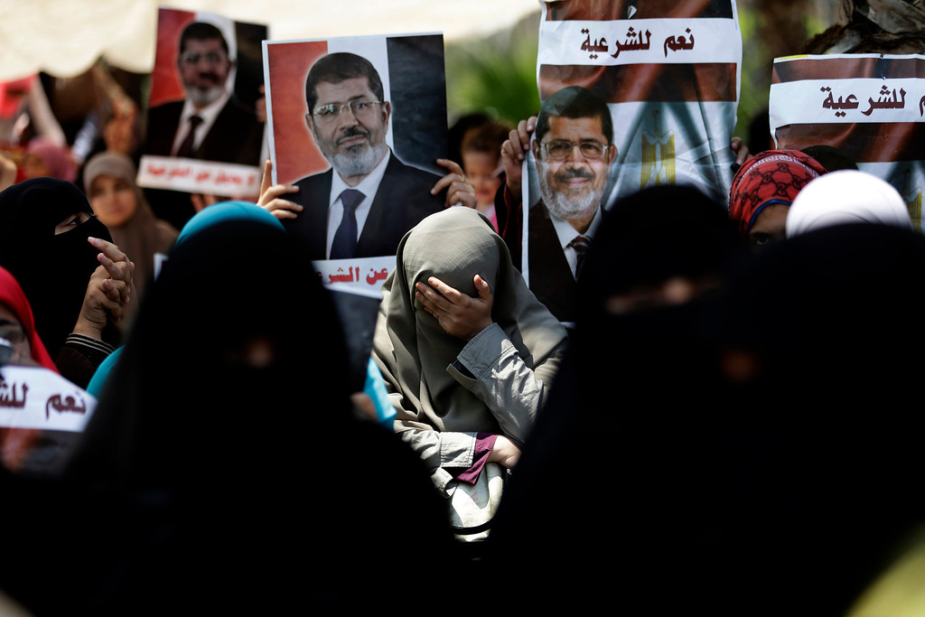 ". A supporter of ousted Egypt\'s President Mohammed Morsi cries during a protest near the University of Cairo, Giza, Egypt, Friday, July 5, 2013. Arabic reads, ""Yes for the legitimacy.\"" Egypt\'s Muslim Brotherhood called for a wave of protests Friday, furious over the military\'s ouster of its president and arrest of its revered leader and other top figures, raising fears of violence and retaliation from Islamic militants. (AP Photo/Hassan Ammar)"