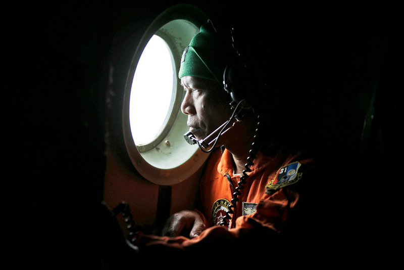 . A crew of an Indonesian Air Force C-130 airplane of the 31st Air Squadron looks out of the window during a search operation for the missing AirAsia flight 8501 jetliner over the waters of Karimata Strait in Indonesia, Monday, Dec. 29, 2014. The Airbus A320-200 vanished Sunday morning in airspace thick with storm clouds on its way from Surabaya, Indonesia, to Singapore. (AP Photo/Dita Alangkara)