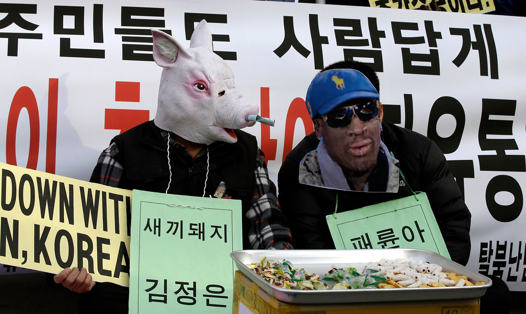 ". A protester wearing a mask of a pig depicting North Korean leader Kim Jong Un, left, and another wearing a mask of former NBA player Dennis Rodman, who is currently in Pyongyang with fellow former NBA players for a basketball game against a team of North Koreans, perform during an anti-North Korea rally on what is believed to be the birthday of  Kim, in Seoul, South Korea, Wednesday, Jan. 8, 2014. More than 100 anti-North Korea protesters and North Korean defectors attended the rally denouncing the North\'s human rights record and nuclear tests. The writing on the left reads ""Little pig, Kim Jong Un.\"" (AP Photo/Lee Jin-man)"