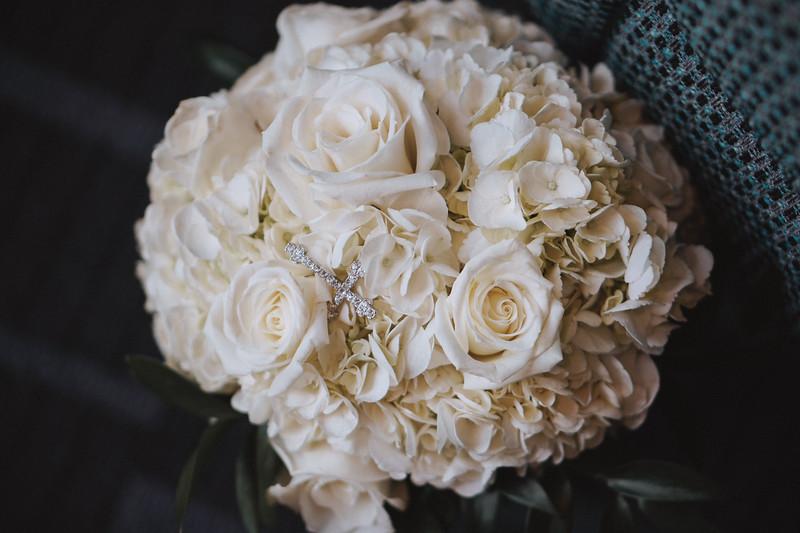 Diamond cross necklace on a bouquet of flowers.