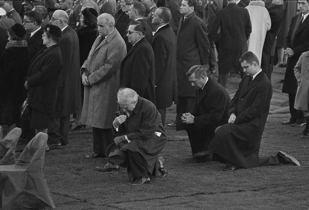 . Mourners kneel as Kennedy is buried at Arlington. Associated Press file