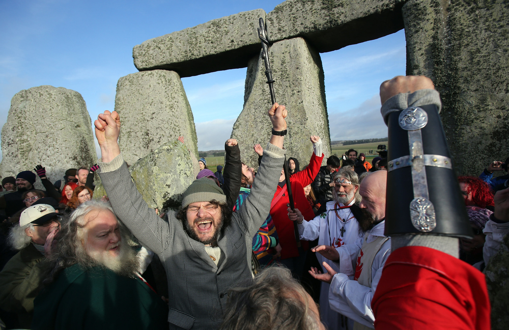 . People cheers as the time passes 11.11am, the time the Mayan Apocalypse was supposed to occur, at a ceremony following the traditional winter solstice celebrations at Stonehenge, on December 21, 2012 in Wiltshire, England. Predictions that the world will end today as it marks the end of a 5,125-year-long cycle in the ancient Maya calendar, encouraged a larger than normal crowd to gather at the famous historic stone circle to celebrate the sunrise closest to the Winter Solstice, the shortest day of the year.  (Photo by Matt Cardy/Getty Images)
