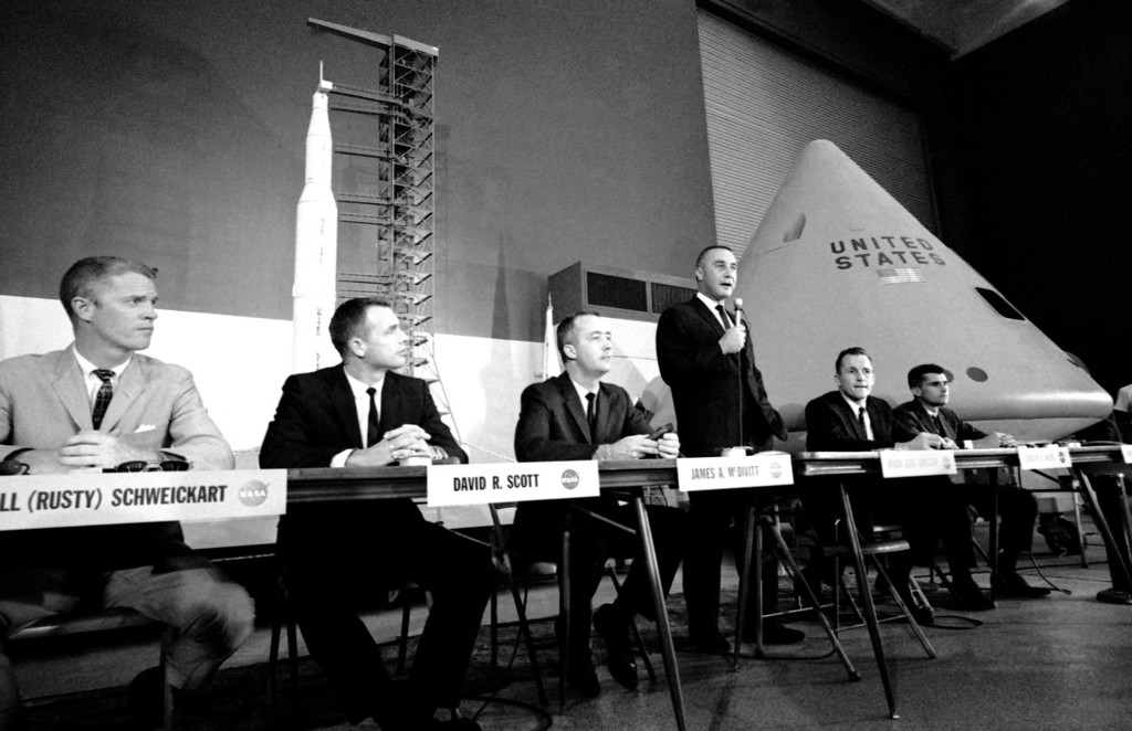 . Command pilot Virgil (Gus) Grissom, at microphone, tells a news conference in Downey, California on August 4, 1966, the 11,000-pound Apollo space craft should be ready to go to Florida next week for final tests. A mockup of the Apollo is in right background. Grissom�s crewmen are Roger B. Chaffee, right, and Edward H. White, second from right. Back-up crew members are, left to right: Rusty Schweickart, David R. Scott and James A. McDivitt. (AP Photo/George Brich)
