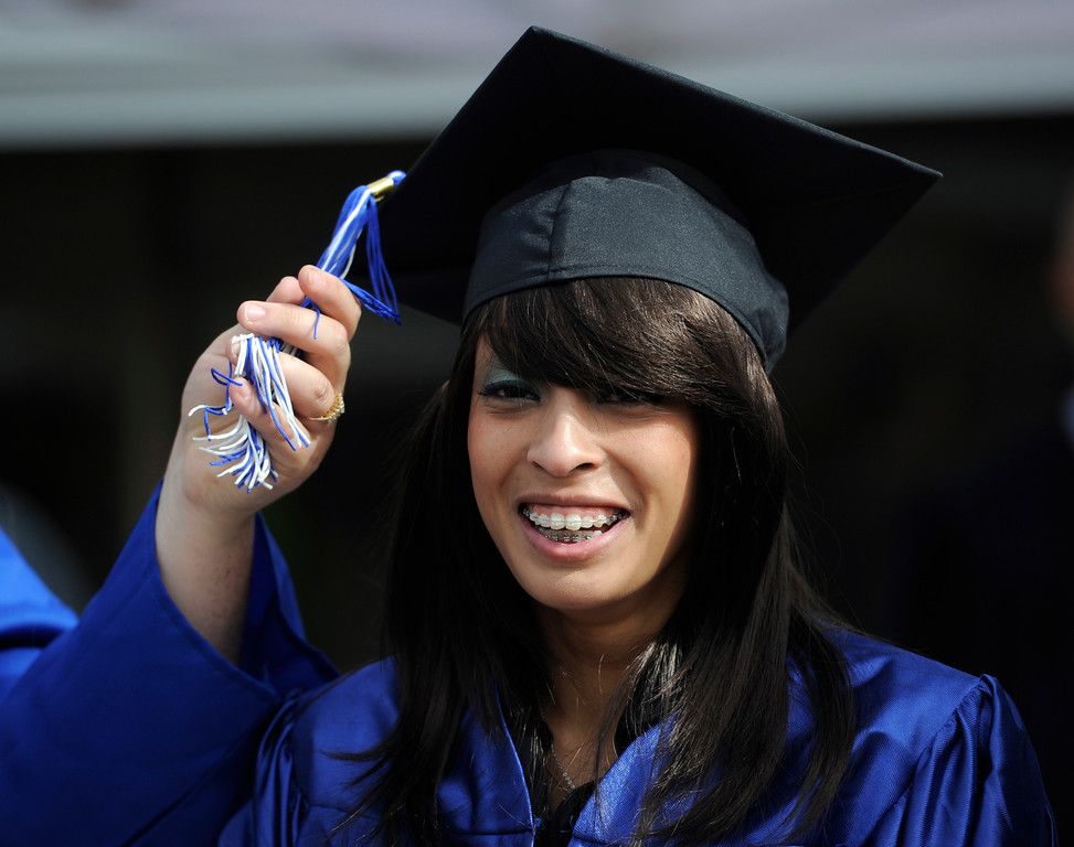 . Graduate Nadia Taylor gets a little help with her tassel from fellow graduate Kandie Gonzales.  (Photo By Kathryn Scott Osler/The Denver Post)
