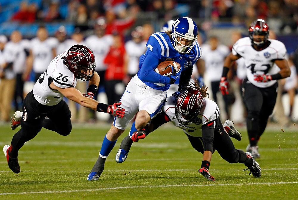 Description of . Duke's Conner Vernon (2) runs after a catch as Cincinnati's Drew Frey (26), Deven Drane (11) and Nick Temple (43) pursue during the first half of the Belk Bowl NCAA college football game in Charlotte, N.C., Thursday, Dec. 27, 2012. (AP Photo/Chuck Burton)