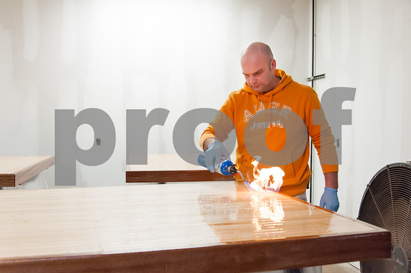 02/09/18 Wesley Bunnell   Staff Work continues on Friday afternoon at Five Churches Brewing at 193 Arch St in New Britain in anticipation of its grand opening that is yet to be determined. Marcin Giera of New Cambridge Painting uses a torch to help eliminate bubbles in the epoxy finish for the table tops which are made from reclaimed bowling alley lanes.