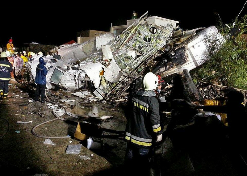 . Rescue workers survey the wreckage of TransAsia Airways flight GE222 which crashed while attempting to land in stormy weather on the Taiwanese island of Penghu, late Wednesday, July 23, 2014.(AP Photo/Wong Yao-wen)