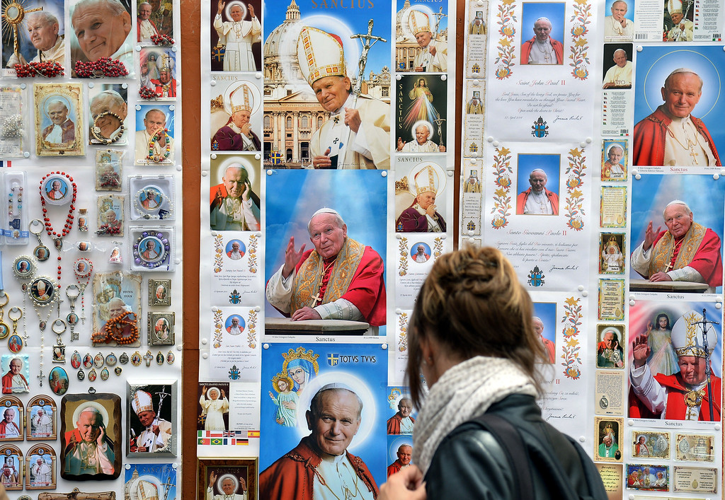 . A woman looks at images of Pope John Paul II, that will be canonized next Sunday, during the Pope Francis\' weekly general audience on April 23, 2014.                (ALBERTO PIZZOLI/AFP/Getty Images)