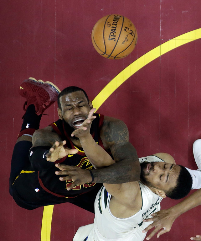 . Cleveland Cavaliers\' LeBron James, left, is stopped by Milwaukee Bucks\' Jabari Parker in the first half of an NBA basketball game, Monday, March 19, 2018, in Cleveland. The Cavaliers won 124-117. (AP Photo/Tony Dejak)