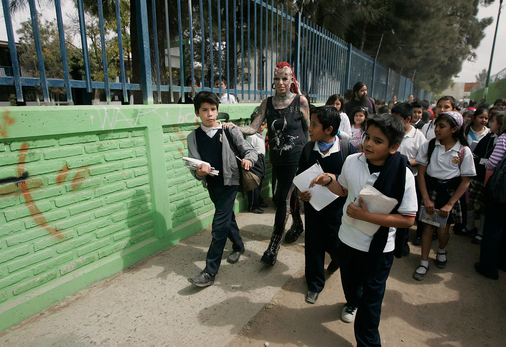 . Maria Jose Cristerna (C) walks with her son Guillermo (L) while being followed by school children outside a school in Guadalajara February 7, 2012. REUTERS/Alejandro Acosta