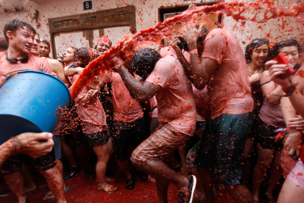 """. People throw tomatoes at each other during the annual \""""tomatina\"""" tomato fight fiesta in the village of Bunol, 50 kilometers outside Valencia, Spain, Wednesday, Aug. 28, 2013. Thousands of people are splattering each other with tons of tomatoes in the annual \""""Tomatina\"""" battle in recession-hit Spain, with the debt-burdened town charging participants entry fees this year for the first time. Bunol town says some 20,000 people are taking part in Wednesday\'s hour-long street bash, inspired by a food fight among kids back in 1945. Participants were this year charged some 10 euros ($13) to foot the cost of the festival. Residents do not pay. (AP Photo/Alberto Saiz)"""