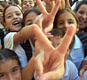 """Mount Olives project image - kids display the hand sign for """"peace""""."""