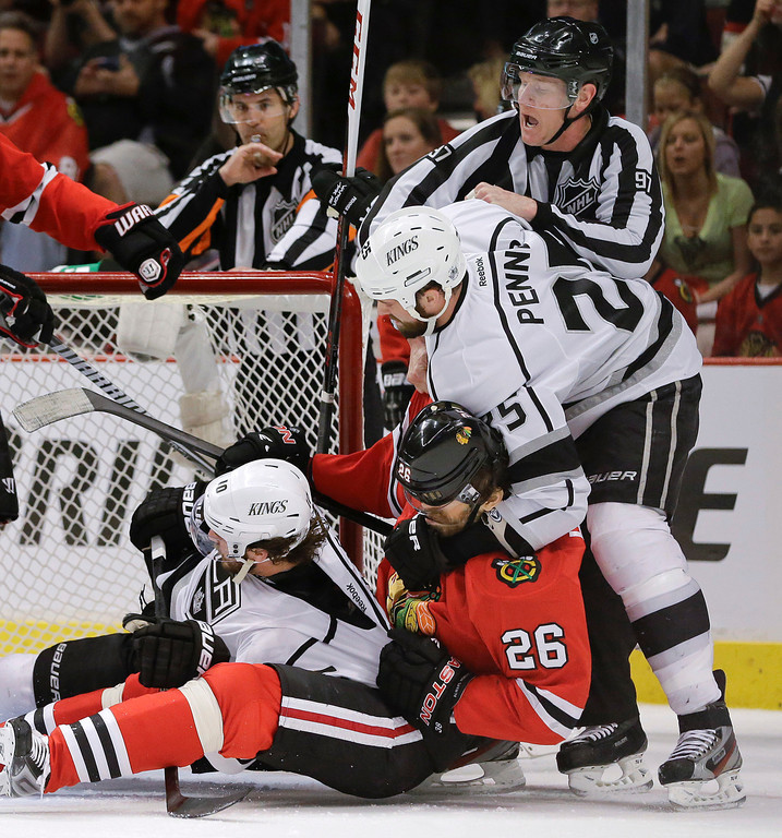 . Los Angeles Kings left wing Dustin Penner (25) grabs Chicago Blackhawks center Michal Handzus (26), who pulls down Los Angeles Kings center Mike Richards (10) during a fight in the first period of Game 1 of the NHL hockey Stanley Cup Western Conference finals, Saturday, June 1, 2013, in Chicago. (AP Photo/Nam Y. Huh)