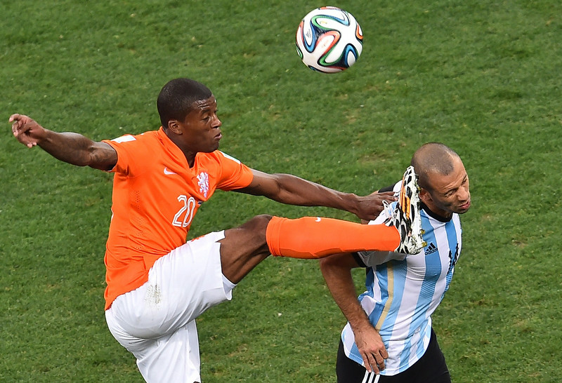 . Netherlands\' midfielder Georginio Wijnaldum (L) kicks next to Argentina\'s midfielder Javier Mascherano during the semi-final football match between Netherlands and Argentina of the FIFA World Cup at The Corinthians Arena in Sao Paulo on July 9, 2014.  (GABRIEL BOUYS/AFP/Getty Images)