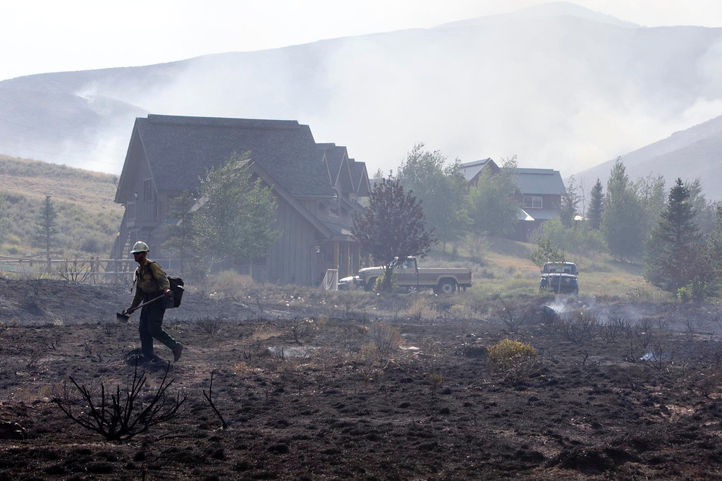 . A firefighter walks across a blackened field near homes on Croy Road and the Rotorun ski hill west of Hailey  Saturday Aug. 17, 2013. The Beaver Creek fire moved through the area in the early hours Saturday morning. (AP Photo/Idaho Statesman, Darin Oswald)