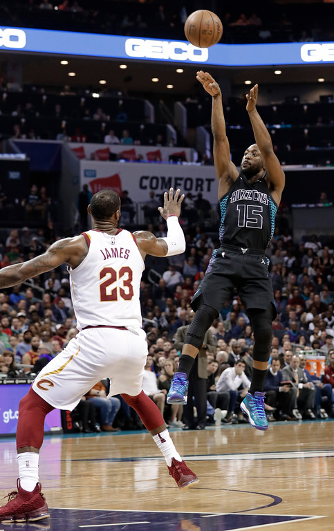 . Charlotte Hornets\' Kemba Walker (15) shoots over Cleveland Cavaliers\' LeBron James (23) during the first half of an NBA basketball game in Charlotte, N.C., Wednesday, March 28, 2018. (AP Photo/Chuck Burton)