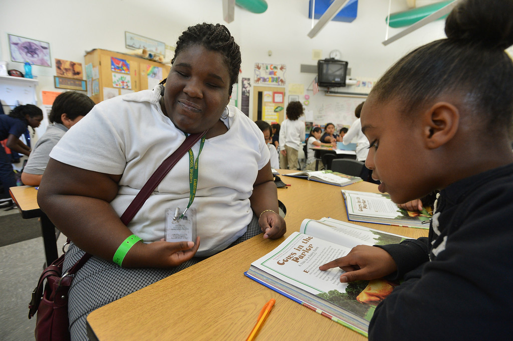 . Hercules High School senior Camille Winfield, who is blind, listens to Khalani Miles read as she works with third grade students on a reading exercise in Sarah Creeley\'s classroom at Hanna Ranch Elementary School in Hercules, Calif., on Thursday, May 30, 2013. Winfield was the only student at Hercules High to receive a Contra Costa Regional Occupational Program award earlier this month for her work in the Careers in Teaching Program. (Kristopher Skinner/Bay Area News Group)
