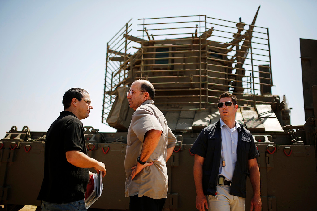 . Israeli Defense Minister Moshe Yaalon (C) stands in front of an armoured personnel carrier (APC) during a visit to a military base near Kibbutz Kissufim outside the central Gaza Strip May 7, 2013. Israel played down weekend air strikes close to Damascus reported to have killed dozens of Syrian soldiers, saying they were not aimed at influencing its neighbour\'s civil war but only at stopping Iranian missiles reaching Lebanese Hezbollah militants. REUTERS/Amir Cohen