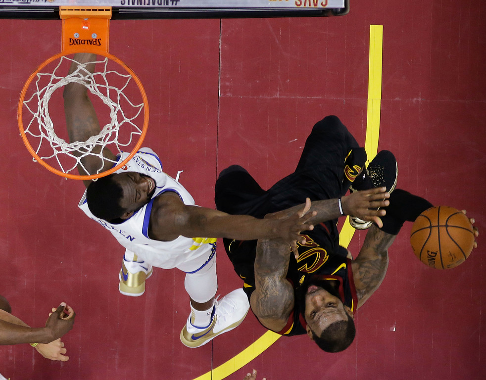 . Cleveland Cavaliers\' LeBron James shoots over Golden State Warriors\' Draymond Green during the first half of Game 4 of basketball\'s NBA Finals, Friday, June 8, 2018, in Cleveland. (AP Photo/Carlos Osorio, Pool)