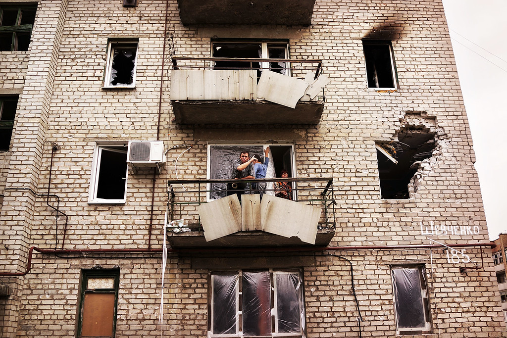 . ALOVAISK, UKRAINE - SEPTEMBER 10:  Residents stand on the balcony of their building which was damaged during heavy fighting in August on September 10, 2014 in Alovaisk, Ukraine. Alovaisk, which is about an hour outside of the separatist held city of Donetsk, saw sustained shelling in August and is still the site of fighting between Ukrainian troops and the Russian backed separatists. (Photo by Spencer Platt/Getty Images)