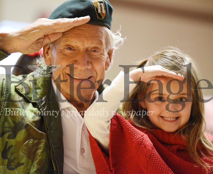 Harold Aughton/Butler Eagle: Former Green Beret Hal Wrigley, a Vietnam Veteran, and granddaughter, Maddison Wrigley, 6, give a salute during the Connoquenessing Valley Elementary School's Veterans Day celebration.