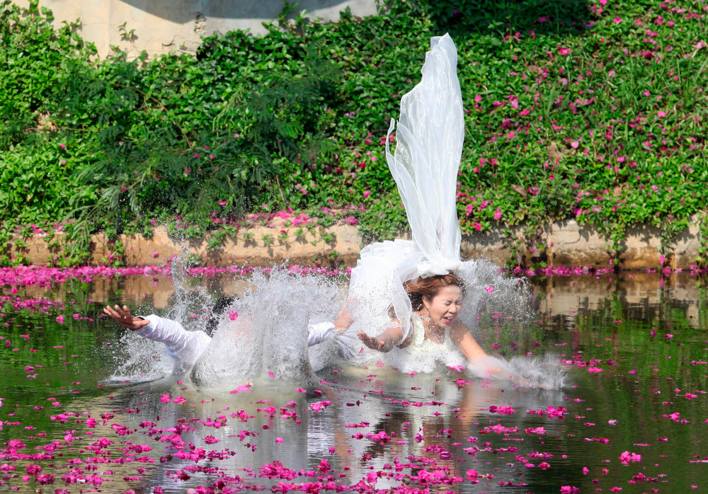 Description of . Thai groom Sopon Sapaotong (L), 41, and his bride Chutima Imsuntear, 37, jump in a pond during a wedding ceremony ahead of Valentine's Day in Prachin Buri province, east of Bangkok February 13, 2013. Three Thai couples took part in the wedding ceremony arranged by a Thai resort that aimed to strengthen the relationships of the couples by doing fun activities.  REUTERS/Kerek Wongsa