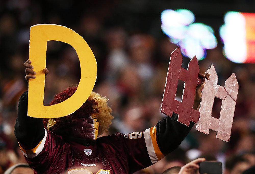 Description of . A Washington Redskins fan hold up signs for defense during their NFC Wild Card Playoff Game against the Seattle Seahawks at FedExField on January 6, 2013 in Landover, Maryland.  (Photo by Win McNamee/Getty Images)