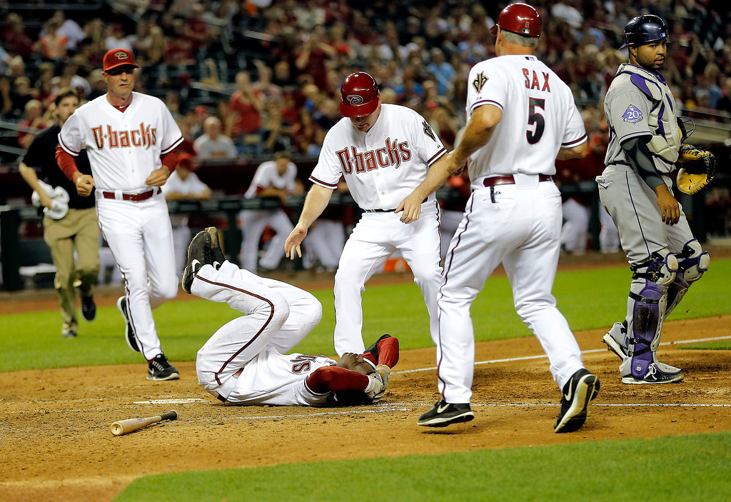 . Arizona Diamondbacks\' Didi Gregorius lies on the ground after being hit in the head by Colorado Rockies pitcher Josh Outman during the seventh inning of a baseball game, Friday, April 26, 2013, in Phoenix. From left are Diamondbacks manger Kirk Gibson, third base coach Matt Williams, fist base coach Steve Sax and Rockies catcher Wilin Rosario.(AP Photo/Matt York)