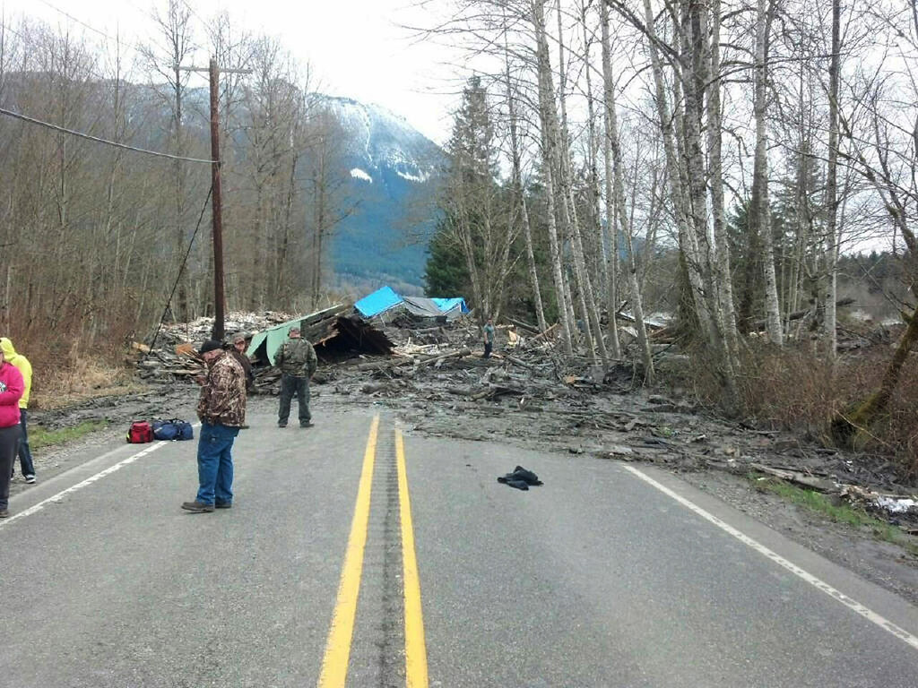 . In this handout from the Washington State Patrol, people stand near a debris from a house that was hit by a mudslide on Highway 530 March 22, 2014 in Snohomish County, Washington.  (Photo by Washington State Patrol via Getty Images)